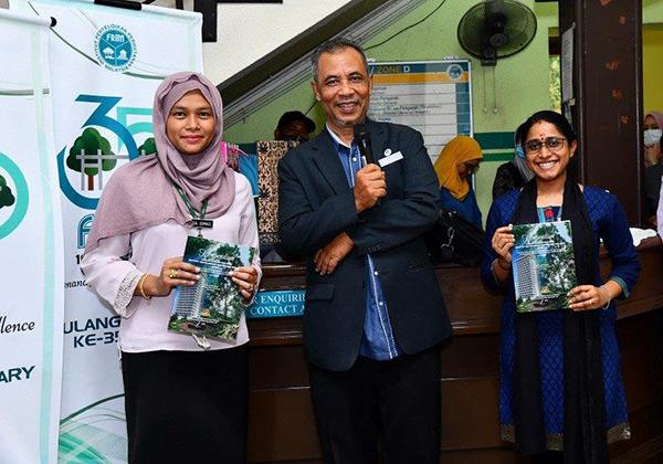Praveena (kanan) dan Liza (kiri) menerima buku 'Kompendium Soalan-soalan Parlimen – Institut Penyelidikan Perhutanan Malaysia (FRIM)' daripada Abd Latif.