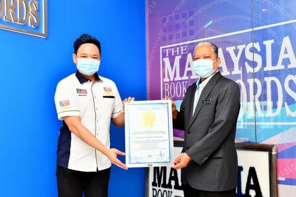 Jwan Heah (kiri) menyampaikan sijil MBR kepada Khali Aziz